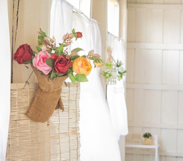 Bukiet kwiatów. i stare drewniane domy, okna z białymi zasłonami i powiew wiatru