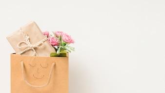 Bukiet kwiatów i zapakowane pudełko w papierowej torbie z ręcznie rysowane twarzy na białym tle