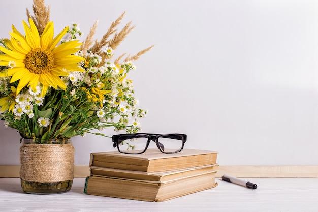 Bukiet kwiatów i zeszyty w okularach na stole.