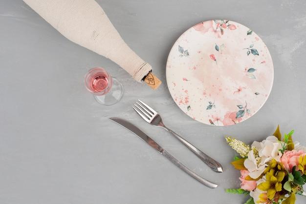Bukiet kwiatów, kieliszek różowego wina i talerz na szarej powierzchni