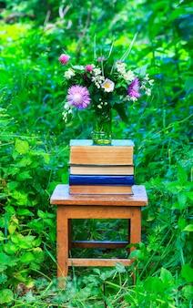 Bukiet kwiatów koniczyny, chabrów i jaśminu w szklanym wazonie i stos książek