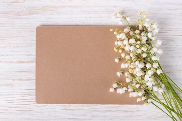 Bukiet kwiatów konwalii i pusty notatnik papierowy na białym drewnianym stole rustykalnym z góry, widok z góry, miejsce na tekst, leżenie na płasko.