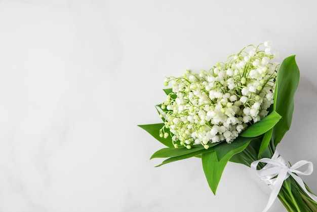 Bukiet kwiatów konwalii na białym marmurze. leżał płasko. widok z góry z miejscem na kopię. koncepcja ślubu