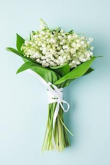 Bukiet kwiatów konwalii na pastelowy błękit. leżał płasko. ślub. orientacja pionowa