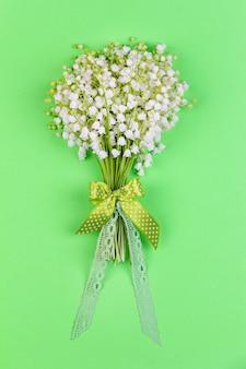 Bukiet kwiatów konwalii z kokardą i wstążką na zielonym tle widok z góry z bliska