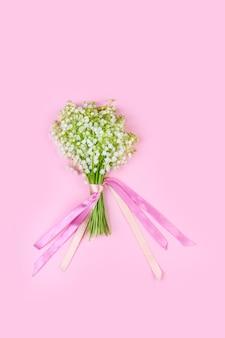 Bukiet kwiatów konwalii z różowymi wstążkami na różowym tle z bliska