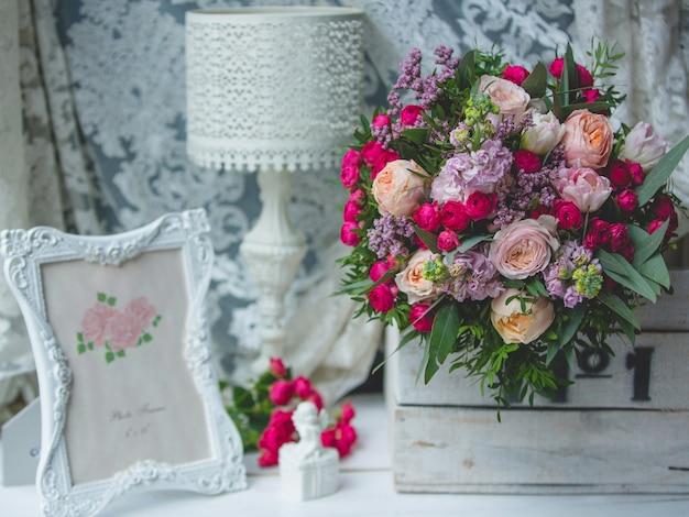 Bukiet kwiatów, lampa do czytania i ramka na zdjęcia