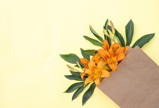 Bukiet kwiatów lilii w torbie rzemieślniczej na żółtym tle. dostawa kwiatów. kompozycja kwiatowa. miejsce na tekst. tło wiosna. leżał płasko. florystyczny. pocztówka na wakacje.