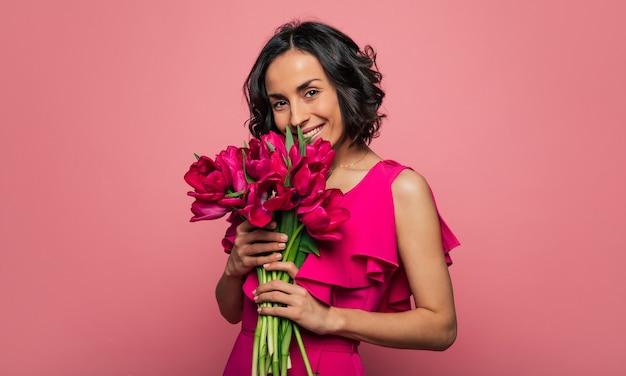 Bukiet kwiatów. młoda brunetka w pięknej sukience wącha bukiet świeżych kwiatów, patrząc w kamerę i uśmiechając się.