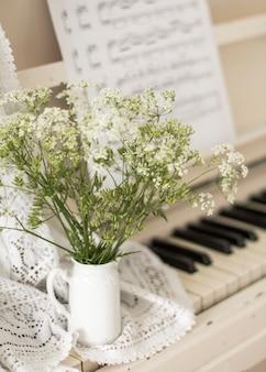 Bukiet kwiatów na białym pianinie z nutami. zdjęcie retro
