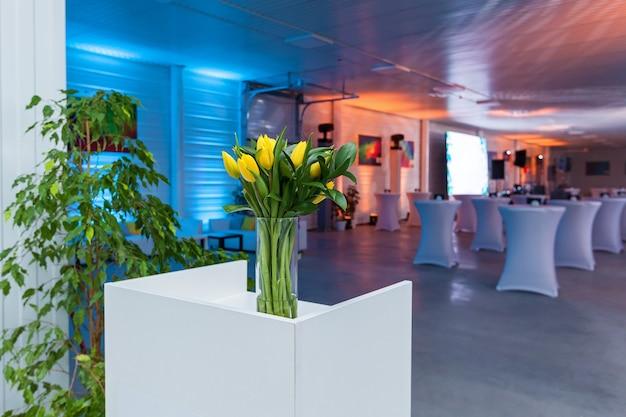 Bukiet kwiatów na białym stole związanym z kokardą