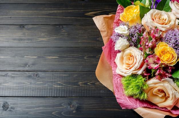 Bukiet kwiatów na ciemnym drewnianym tle. bukiet z różami.