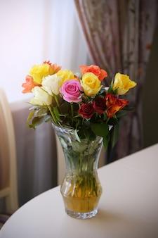 Bukiet kwiatów na drewnianym stole. ikiebana w przezroczystym szklanym wazonie.