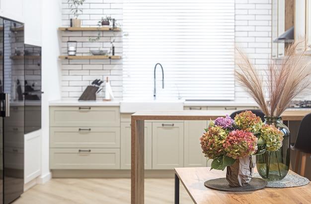 Bukiet kwiatów na tle wnętrza nowoczesnej kuchni w stylu skandynawskim.