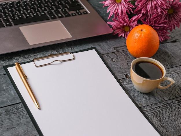 Bukiet kwiatów, notatnik, filiżanka kawy, pomarańcza i długopis na ciemnym rustykalnym stole. widok z góry.