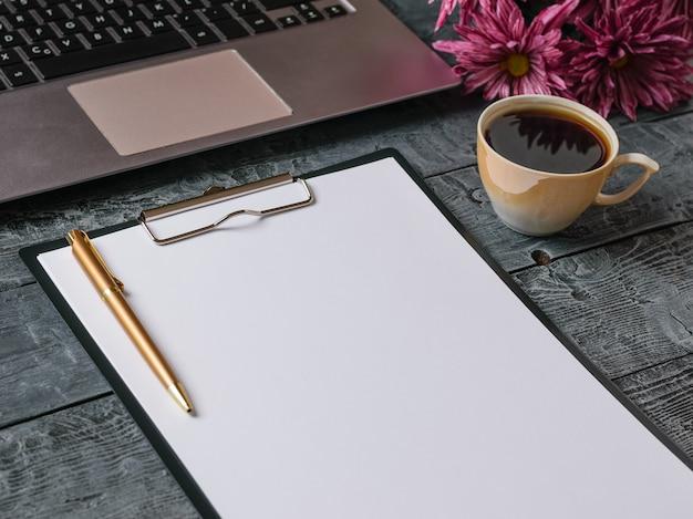 Bukiet kwiatów, notatnik, kawa i długopis na drewnianym stole