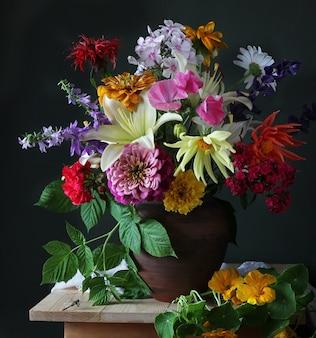 Bukiet kwiatów ogrodowych w glinianym dzbanku i ważce.