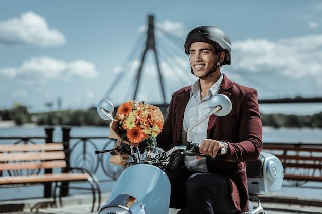 Bukiet kwiatów. optymistyczny wesoły facet mający bukiet kwiatów i jeżdżący na motocyklu
