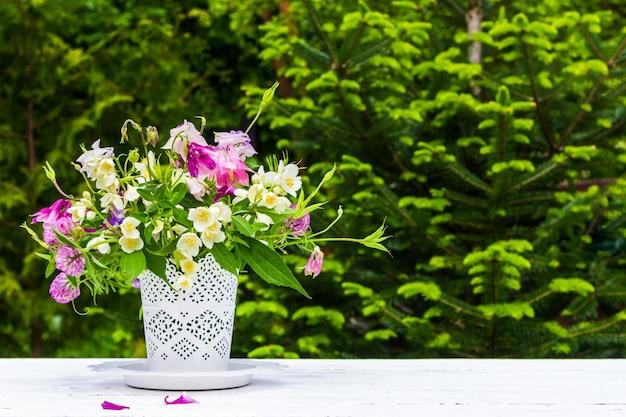 Bukiet kwiatów orlików, jaśminu i koniczyny w białym wazonie na białym stole