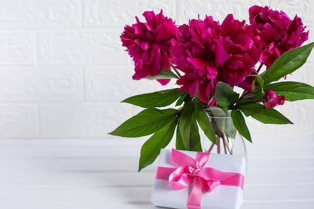 Bukiet kwiatów piwonii i pudełko na stole