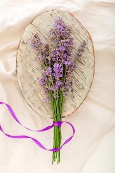 Bukiet kwiatów świeżej lawendy na starej rustykalnej drewnianej desce na tkaninie. bukiet lawendy przewiązany wstążką. flatlay francuski kwiat w stylu prowansalskim. suszenie kwiatów lawendy.