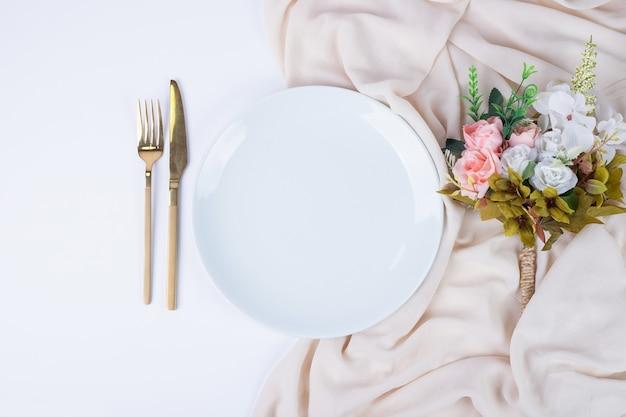 Bukiet kwiatów, talerz i sztućce na białej powierzchni.