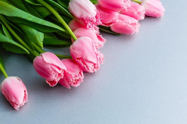 Bukiet kwiatów tulipanów różowy na szarym tle leżał płasko.