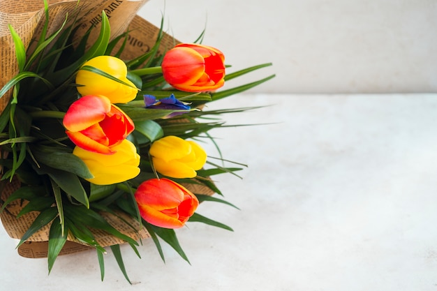 Bukiet kwiatów tulipanów w paczce papieru na stole