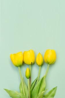 Bukiet kwiatów tulipanów żółty na tle mięty. widok płaski świeckich, z góry z copyspace.
