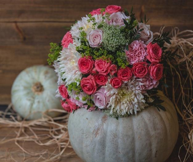 Bukiet kwiatów umieszczony w kuli dyni