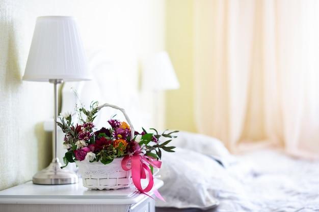 Bukiet kwiatów w białym koszu z jasnym wnętrzem sypialni