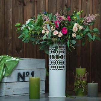 Bukiet kwiatów w białym wazonie dekoracyjnym.