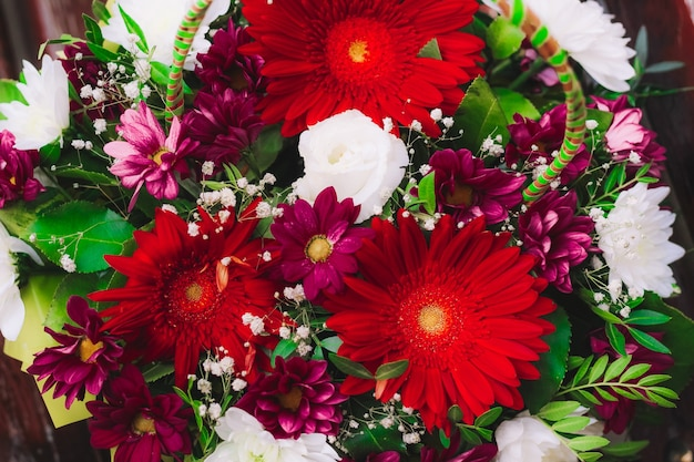 Bukiet kwiatów w czerwonych kolorach. gerbera, chryzantema, eustoma, gipsówka. zamknij widok
