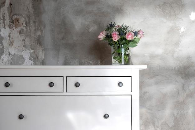 Bukiet kwiatów w pokoju na komodzie.