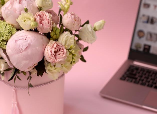 Bukiet kwiatów w pudełku zbliżenie na tle otwartego laptopa selektywna ostrość róże hortensji i piwonie na różowym tle koncepcja dostawy do domu kupowanie kwiatów online