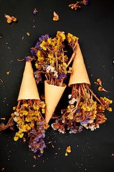 Bukiet kwiatów w rożek waflowy na czarnym tle.