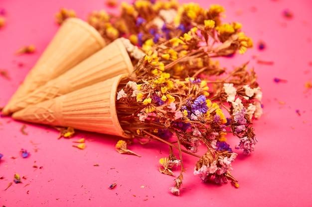 Bukiet kwiatów w rożku waflowym na różowym tle.