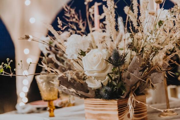 Bukiet kwiatów w stylu boho, udekoruj świąteczny stół, suszone kwiaty, białe róże, koncepcja florystyczna.