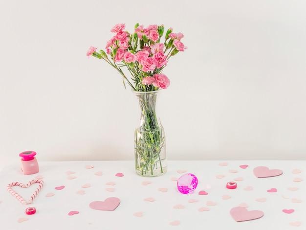 Bukiet kwiatów w wazonie w pobliżu zestaw papierowych serc i laski cukierki
