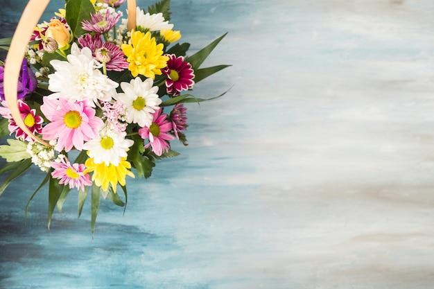 Bukiet kwiatów w wiklinowym koszu na stole