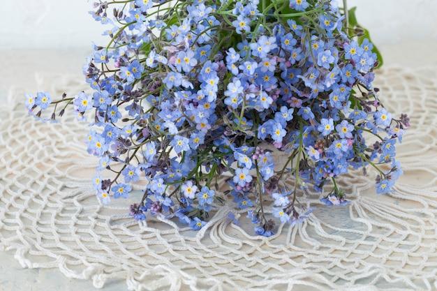 Bukiet kwiatów zapomnij mi nots na stole