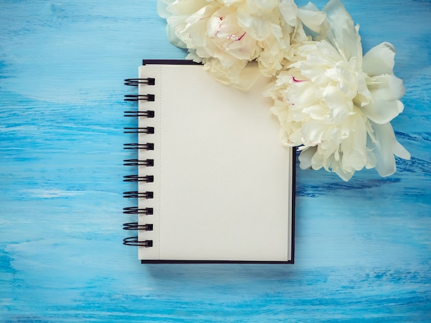 Bukiet kwitnących, białych piwonii i pustej strony notatnika