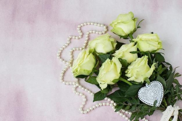 Bukiet lekkich róż, białego maswerku serca i pereł koraliki na różowym tle