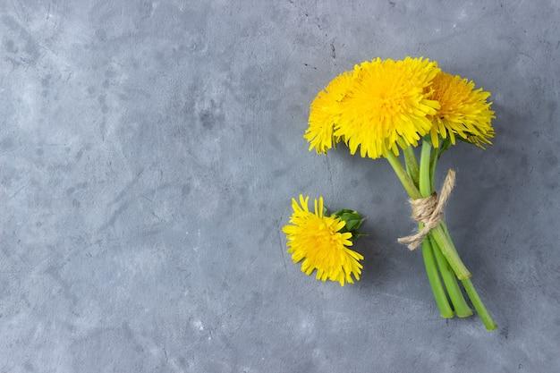 Bukiet letnich kwiatów mniszka lekarskiego na szarym tle. widok z góry z miejsca na kopię.