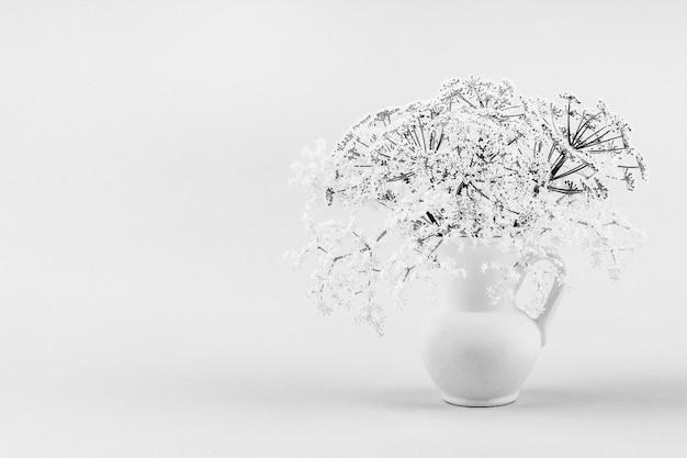 Bukiet małych delikatnych białych kwiatów czarnego bzu w białym dzbanku