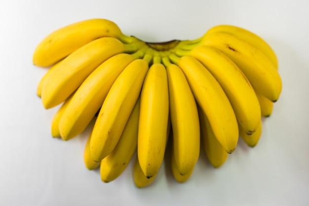 Bukiet małych dojrzałych bananów na białym tle