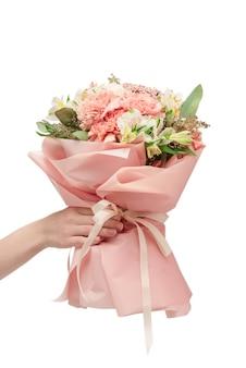 Bukiet miękkich różowych kwiatów w różowym papierze do pakowania w rękach kobiety na białym tle na białej powierzchni