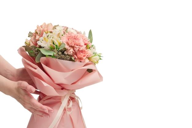 Bukiet miękkich różowych kwiatów w różowym papierze pakowym w ręce kobiety na białym tle na białej powierzchni.