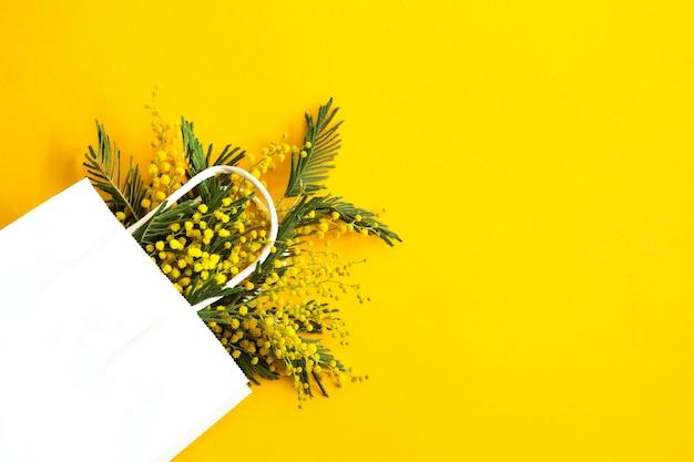 Bukiet mimozy w białej torebce prezentowej.