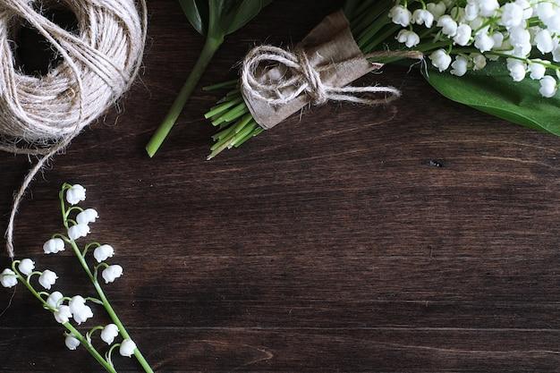 Bukiet młodych konwalii na drewnianym stole